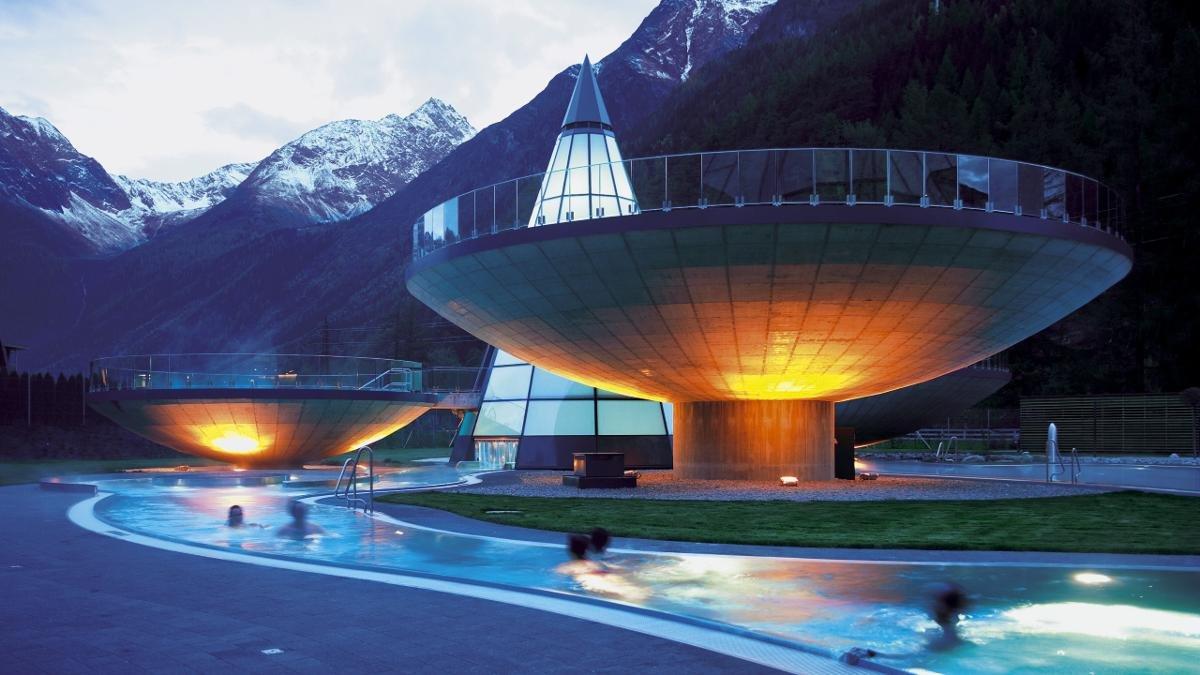 Tout autour d'une tour de verre en forme de cône où se reflètent les montagnes avoisinantes, les bassins extérieurs des thermes déploient leurs contours hémisphériques., © Ötztal Tourismus